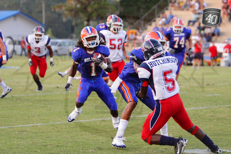 Taylor County RB #1 T. Jackson looks for extra yards, while Wakulla DB #5 D. Hutchinson tries to make a tackle.